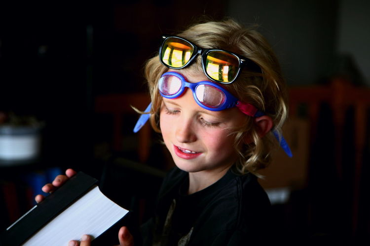 Close-up of boy holding book with glasses on forehead