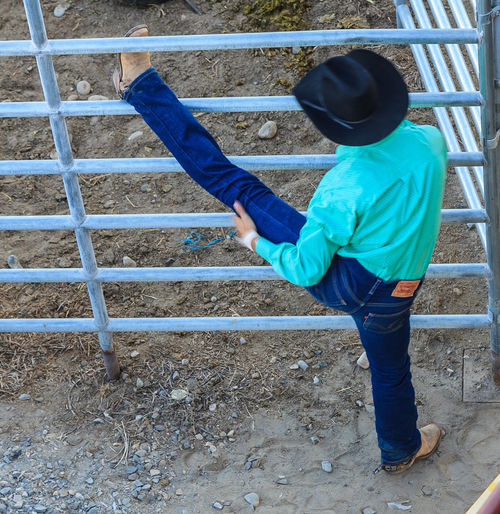 Rear View Of Cowboy Stretching Legs On Fence At Field