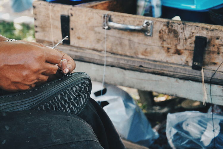 Cropped image of man repairing shoe