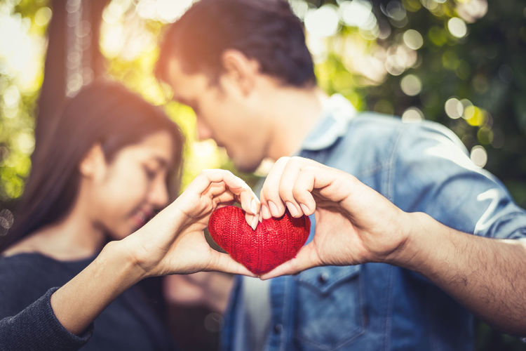 Couple holding heart shape standing at park