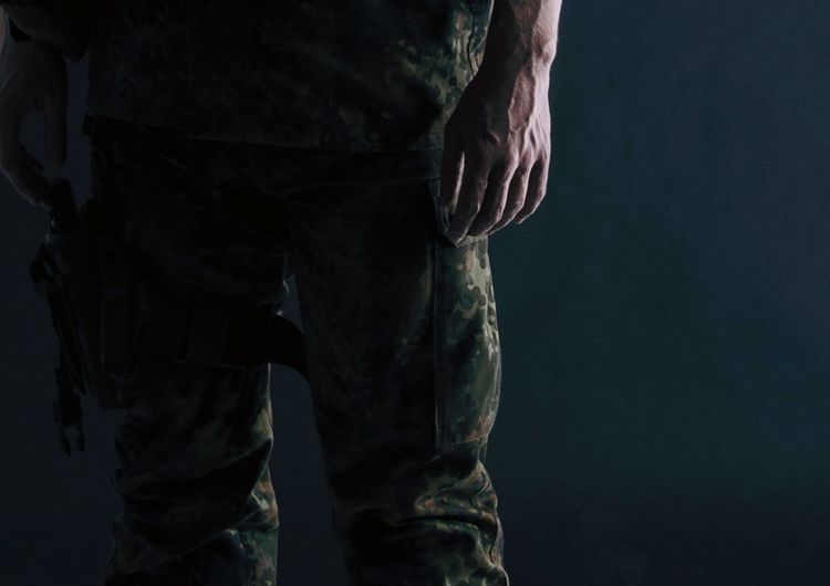 Midsection Of Army Soldier Standing Against Black Background