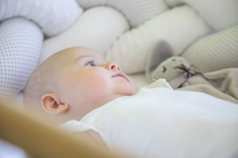 Cute baby lying on bed at home