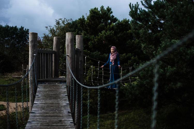Woman standing on footbridge against trees