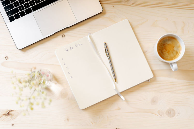 Top view blank paper notebook with to do list, laptop keyboard, cup of coffee and pen. desktop mocku