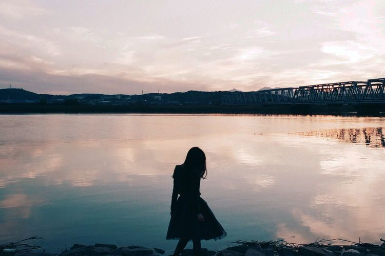 Silhouette girl standing by lake against sky during sunset