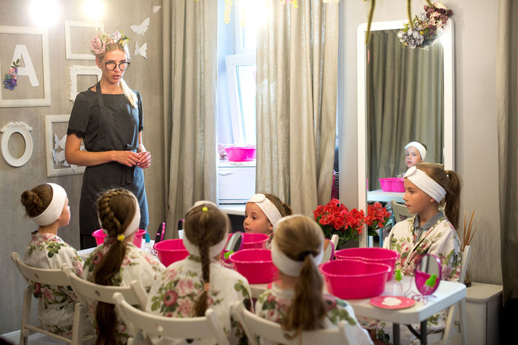 Beautician talking to children at spa during birthday party