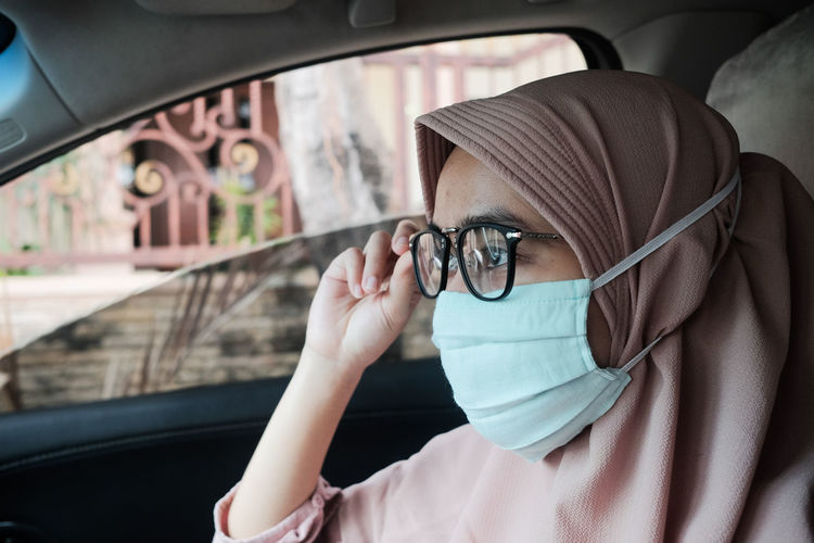 Close-up of woman wearing mask sitting car