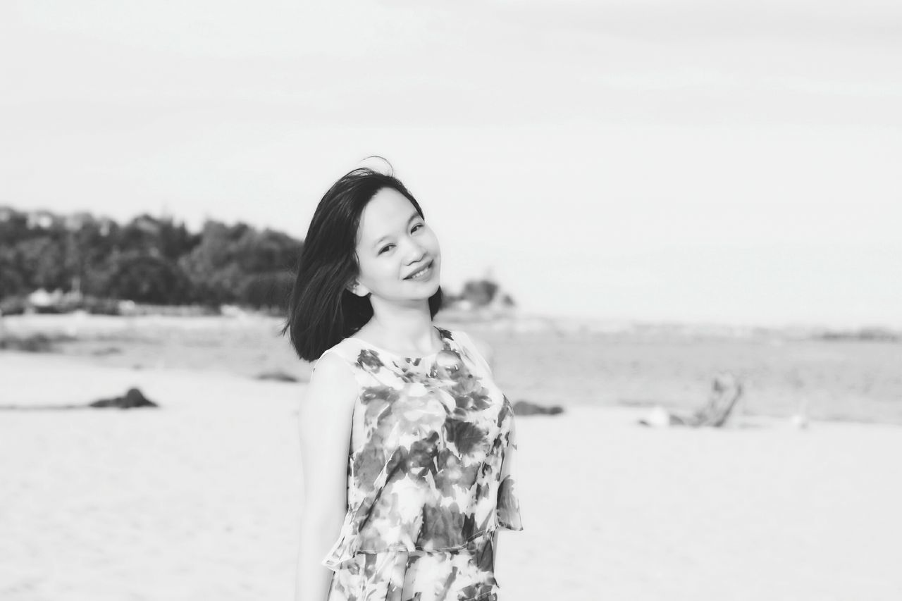 Portrait Of Young Woman Standing At Beach Against Sky