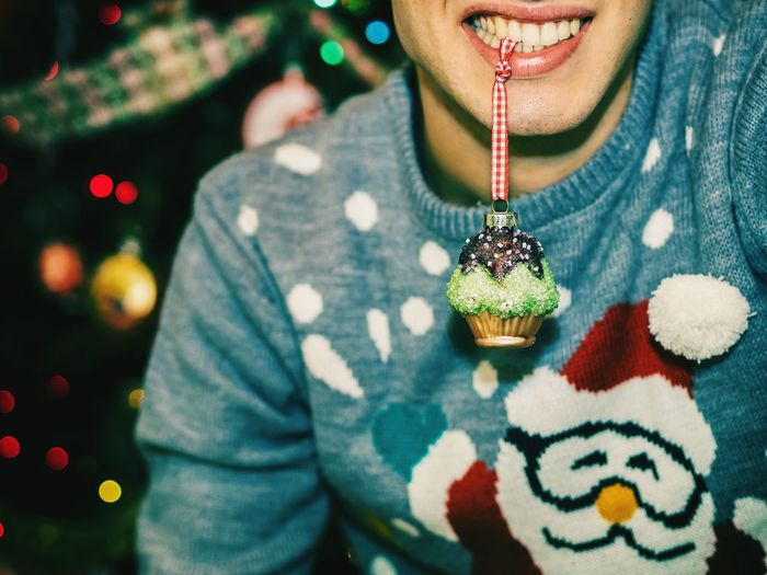 Midsection Of Man Holding Christmas Decoration In Mouth