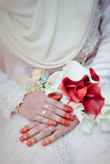 Close-up of bride holding bouquet of rose