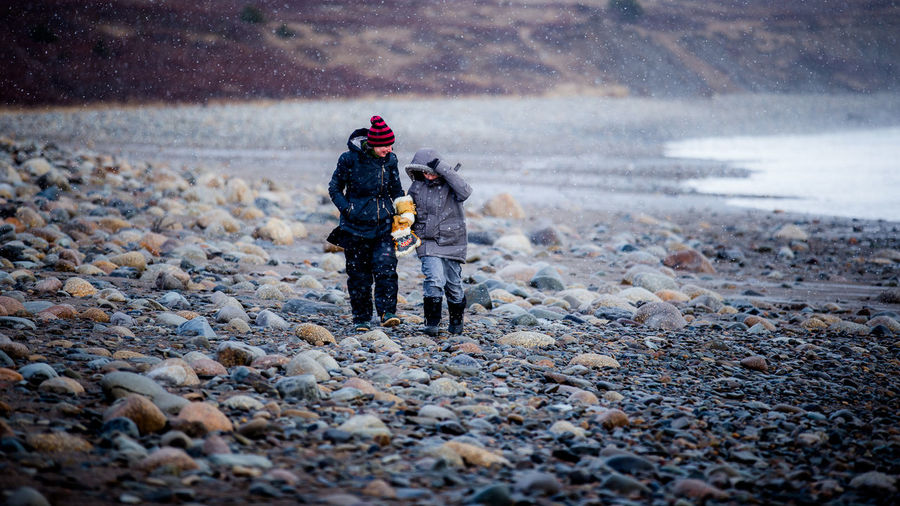 Full length of mother walking with son at beach during winter