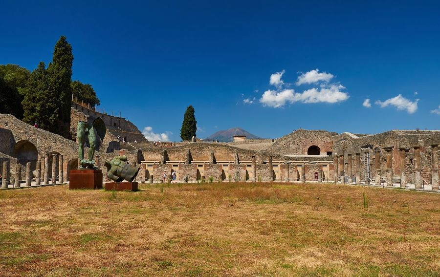 Pompeii with modern art installations and Vesuvius in the background Italy Pompeii  Ruins Columns Vesuvius  Blue Sky Abandoned Ancient Architecture Historic Walls Iconic Grass Museum Outdoors Travel Destinations Old Ruin Ancient Civilization Trees Clouds