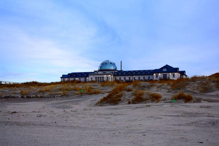 Built structure on beach against blue sky