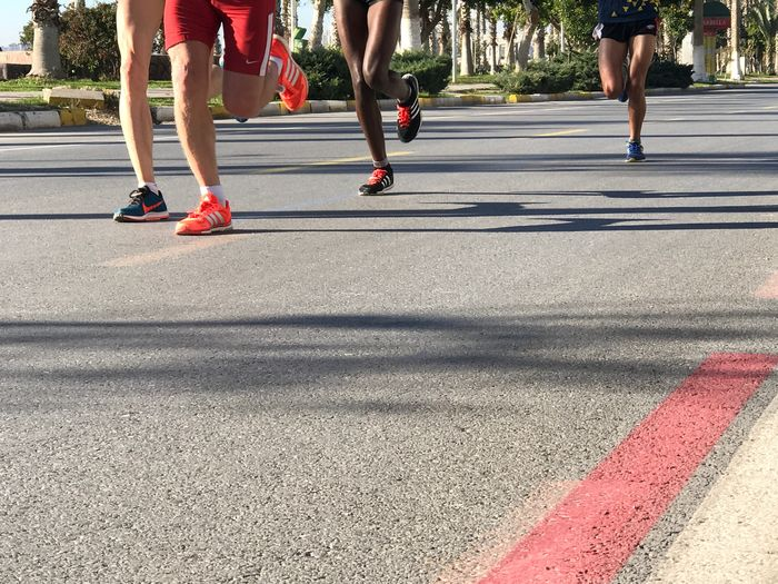Low section of people running on road