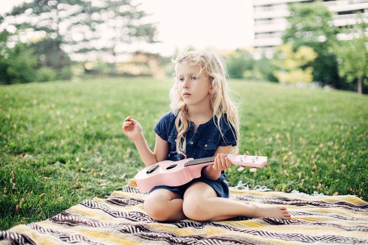 Full length of a girl sitting on grass
