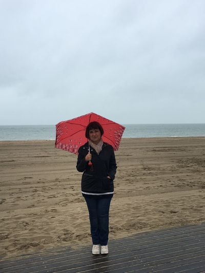 Portrait Of Mature Woman With Umbrella Standing At Beach Against Sky