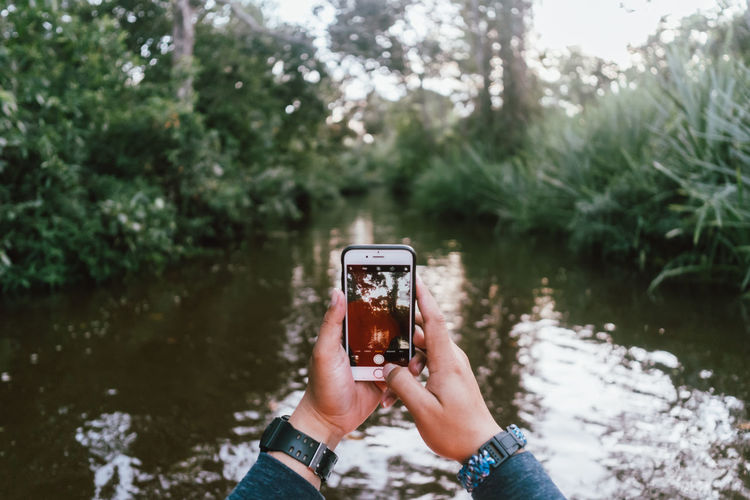Man holding camera while standing by lake