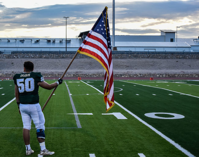 Rear view of man and flag against sky