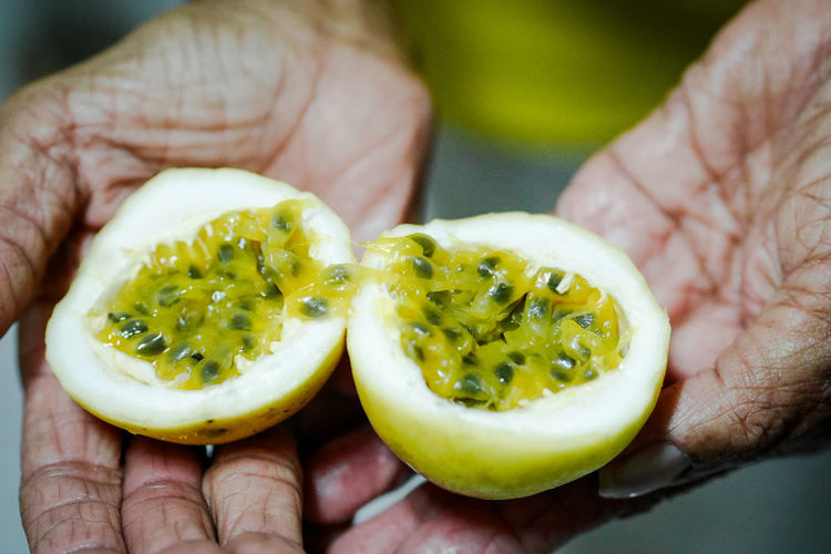 Close-up of hand holding passion fruit