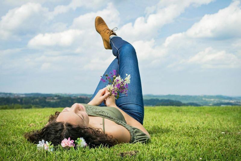 Woman lying on field against sky