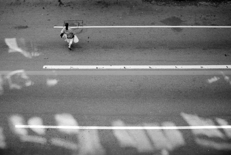EyeEm Best Shots Eye4photography  Getting Inspired Aerial View Streetphotography Urban Urban Geometry Urbanphotography Light And Shadow Lines Asphalt Blackandwhite Streetphoto_bw B&w b&w street photography Monochrome One Person Road City Full Length Road Marking High Angle View Outdoors Motion Street The Street Photographer - 2019 EyeEm Awards