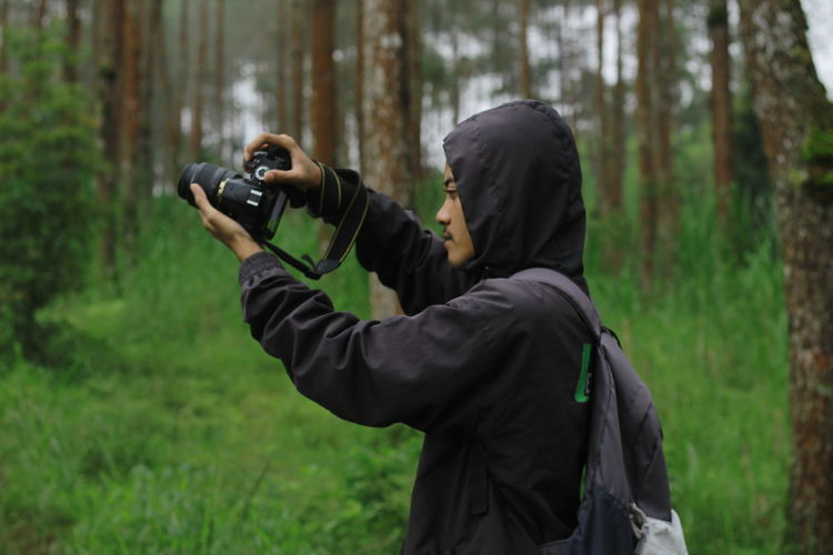Full length of man photographing in forest