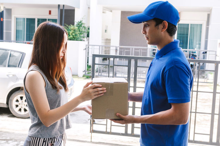 Woman accepting a delivery boxes from delivery man Adult Architecture Casual Clothing Communication Day Emotion Hairstyle Holding Men People Real People Side View Standing Three Quarter Length Togetherness Two People Women Young Adult Young Men Young Women