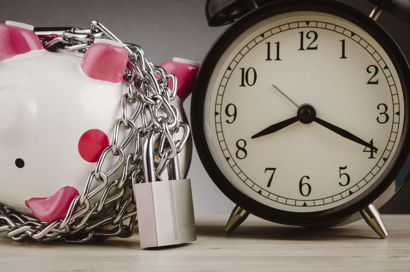 piggy bank surrounded by chains and padlock on wooden desk Clock Time Still Life Indoors  Table No People Alarm Clock Close-up Large Group Of Objects Number Heart Shape Communication Finance Instrument Of Time Business Shape Piggy Bank Wealth Savings Pink Color Minute Hand Clock Face