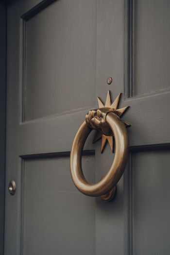 Close up of a metal door knocker on a wooden front door of a house.
