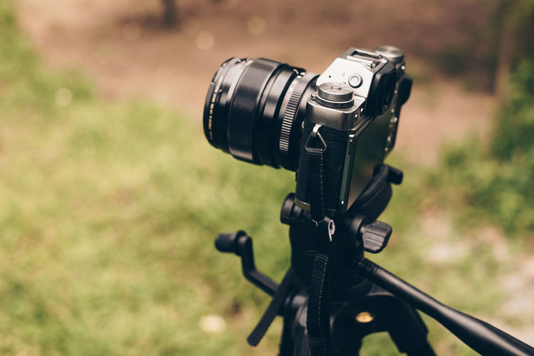 mirrorless camera on a tripod Focus On Foreground Technology Close-up Photography Themes No People Day Camera - Photographic Equipment Metal Black Color Lens - Optical Instrument Field Outdoors Photographic Equipment Camera Nature Grass Land Selective Focus Digital Camera Backgrounds Copy Space Mirrorless SLR Camera Tripod Lens It's About The Journey