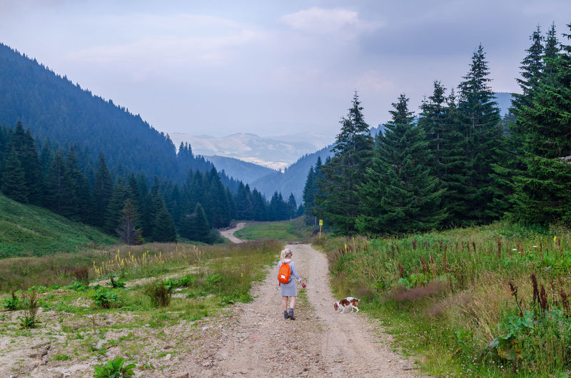 Woman hiker and her dog while walking on a path leading through hills