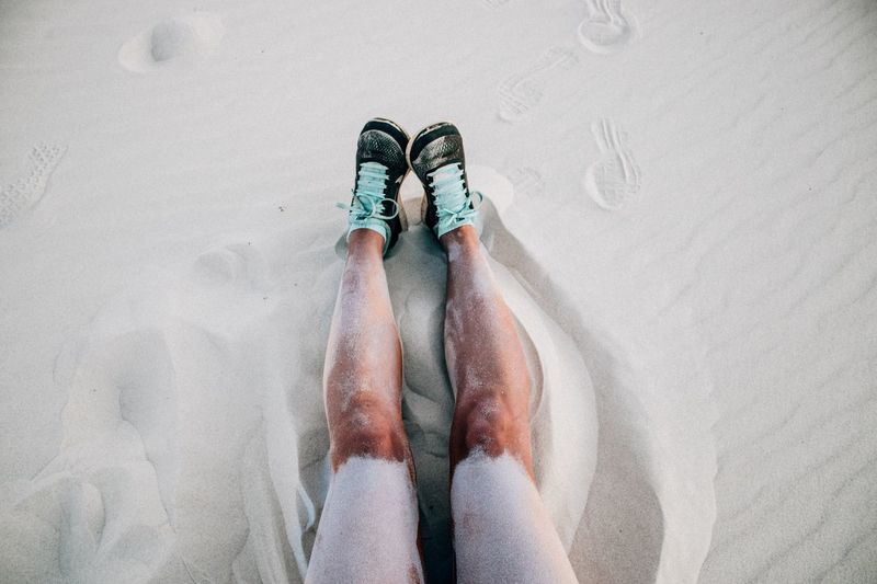 Legs of a woman sitting on sand