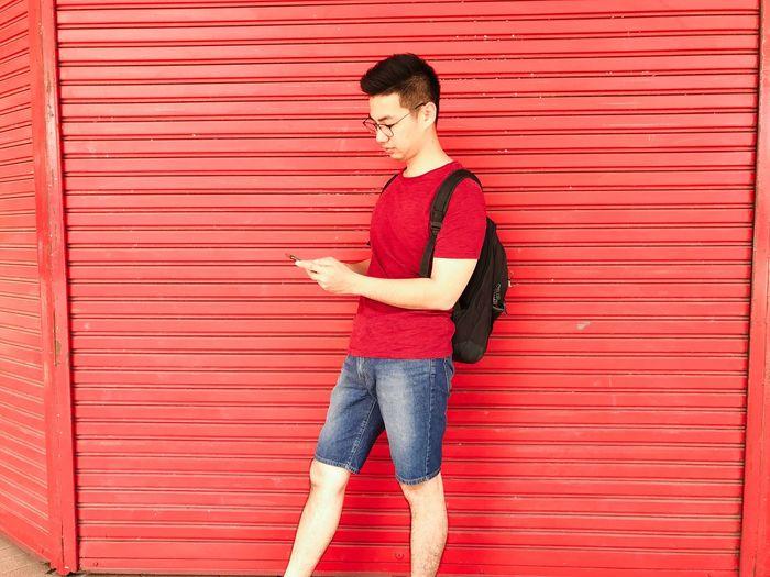 Man wearing shorts using smart phone against shutter