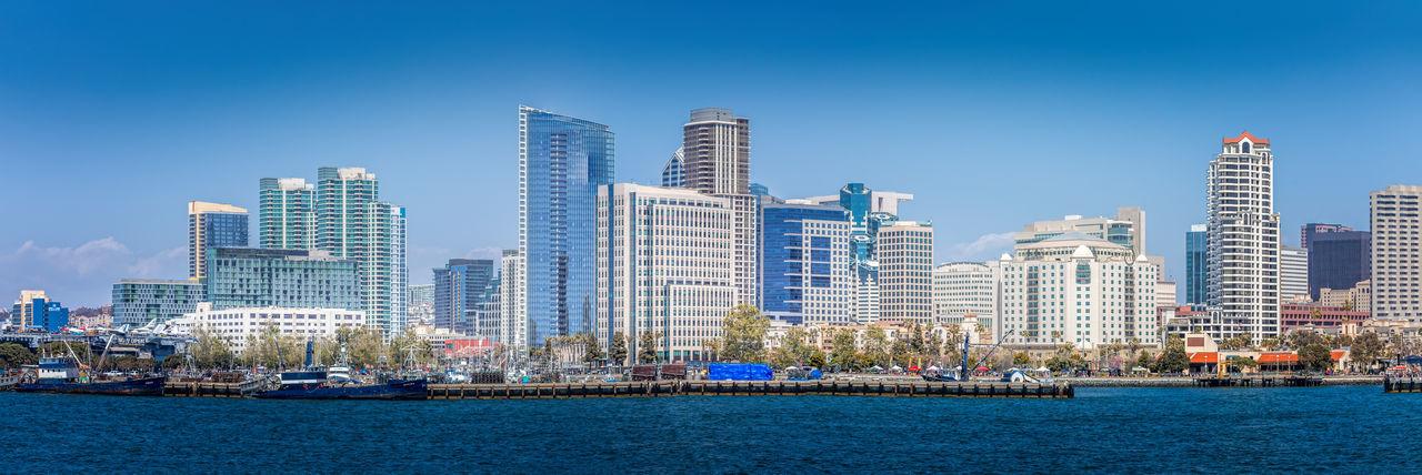 Modern buildings in city against clear blue sky