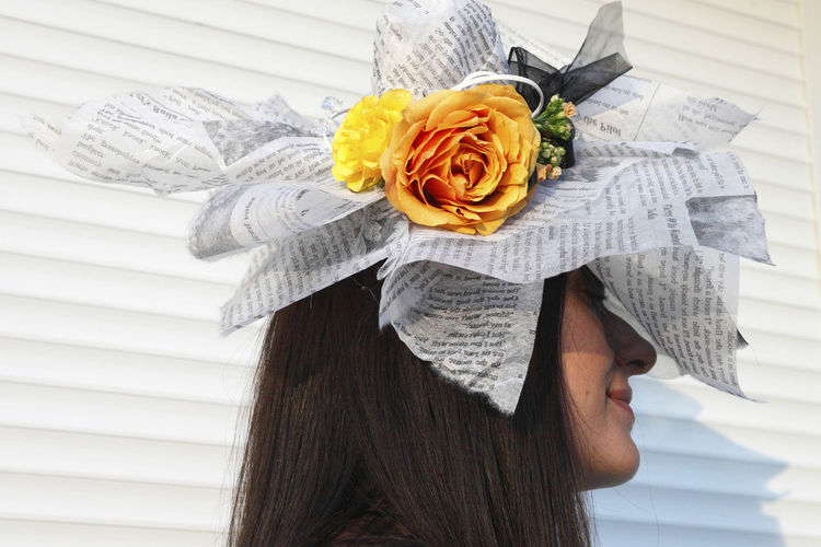 Close-up of smiling young woman wearing paper hat with artificial flowers against white wall
