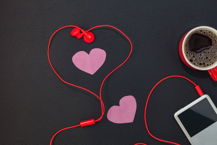 Close-Up Of Red Headphones Connected To Ipod Over Black Background