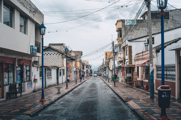 A street from a small town in Ecuador named Cotacachi, where live some indigenous people of the country. Bad Weather Imbabura Architecture Building Building Exterior Built Structure Cable City Day Diminishing Perspective Direction Electricity  No People Outdoors Power Supply Rain Residential District Road Sign Sky Small Town South America Street The Way Forward Transportation The Street Photographer - 2018 EyeEm Awards