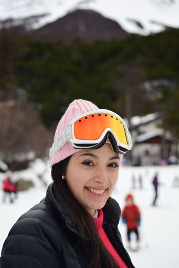 Portrait Of Smiling Woman In Ski Goggles Against Mountains