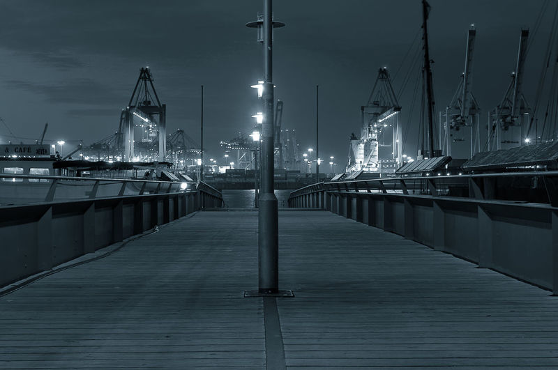 Illuminated street lights on bridge at commercial dock during night