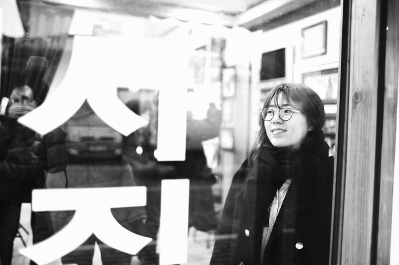 Black And White Window Real People EyeEm People Only Women The Week On Eyem EyeEm Best Shots Rear View Photo One Person Smiling Young Women Lifestyles Store Window Store Reflection Leisure Activity Young Adult Indoors  Day Adult