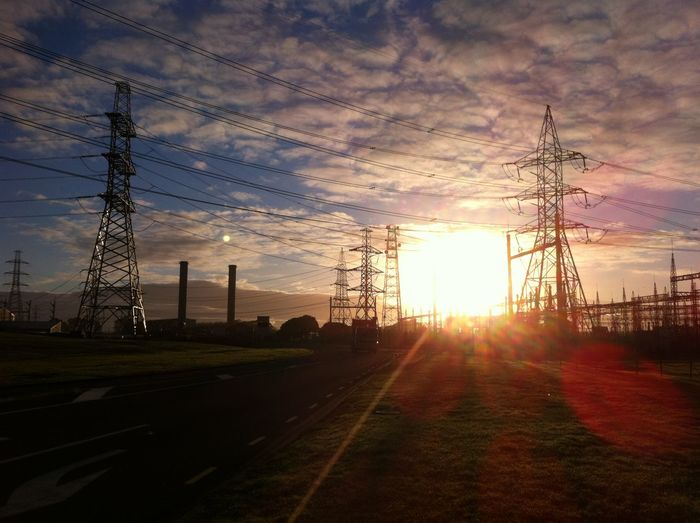 Electricity pylons on country road against cloudy sky