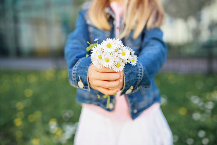 Flower Flowering Plant Holding One Person Plant Freshness Nature Midsection Casual Clothing Front View Focus On Foreground Blond Hair Day Standing Fragility Leisure Activity Outdoors Flower Head Bouquet Girl Child Daisy Springtime Spring