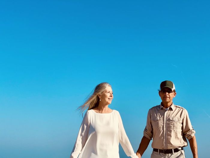Active senior couple holding hands as they walk together against blue sky. waist up and copy space.