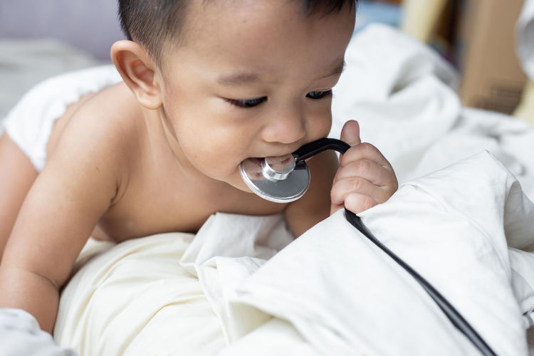 Cute baby boy biting stethoscope while lying on bed at home