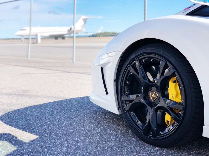 Lamborghini Transportation Mode Of Transportation Land Vehicle Motor Vehicle No People Day Car Close-up Wheel Airport Air Vehicle Tire Nature Road Travel Focus On Foreground White Color Airplane Outdoors Blue