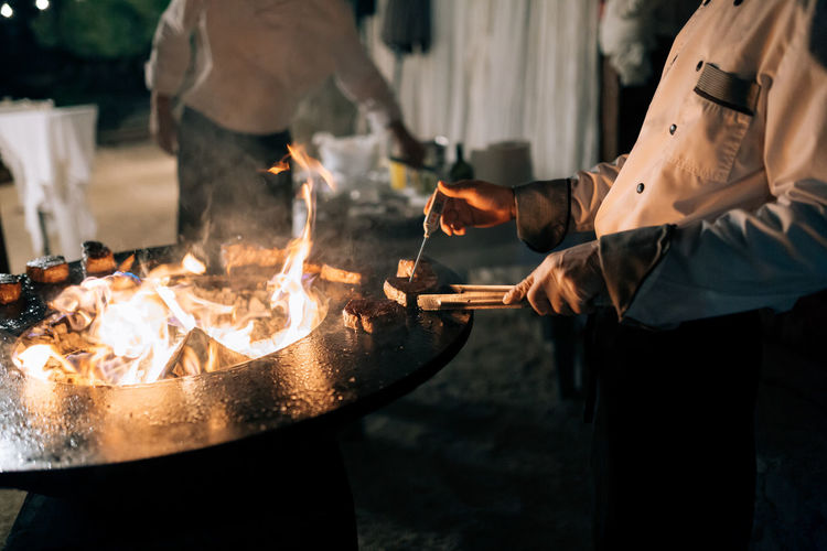 People working on barbecue grill