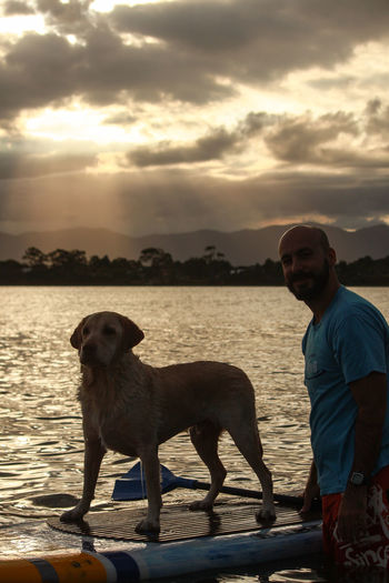Portrait of man with dog standing against sky during sunset