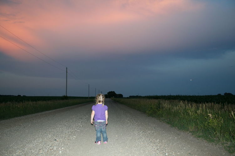Rear view full length of girl standing on road amidst grassy field against sky during sunset