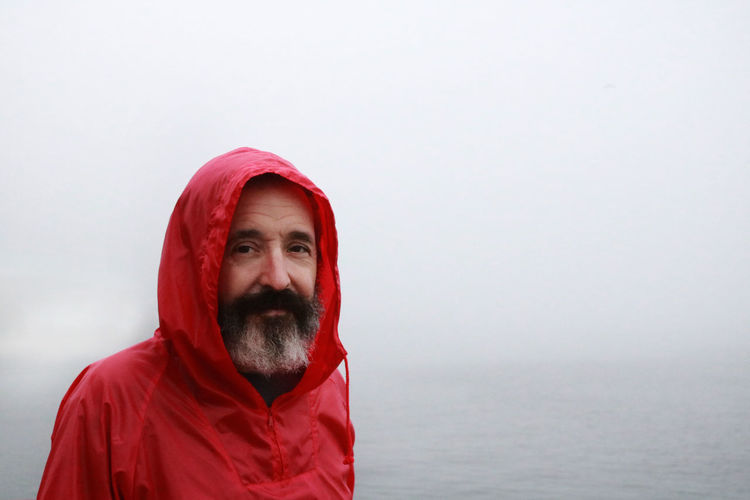 Portrait of man in red jacket against sea