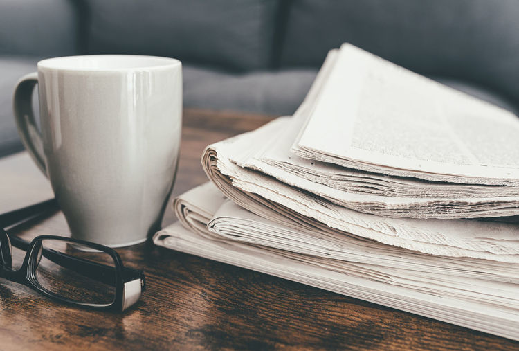 Close-up shot of stack of newspapers, coffee mug and glasses on living room table
